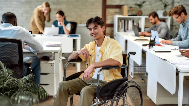 Young Asian man smiling in a wheelchair in a very busy office.