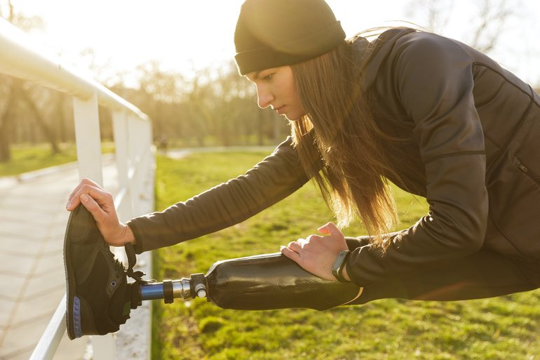 A young amputee runner rests her artificial leg against a wooden fence