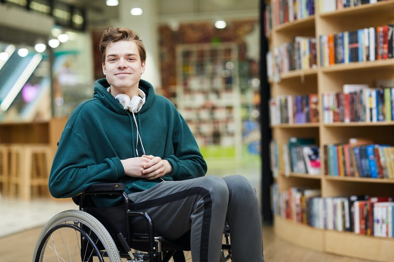 Young man in a wheel in a modern library