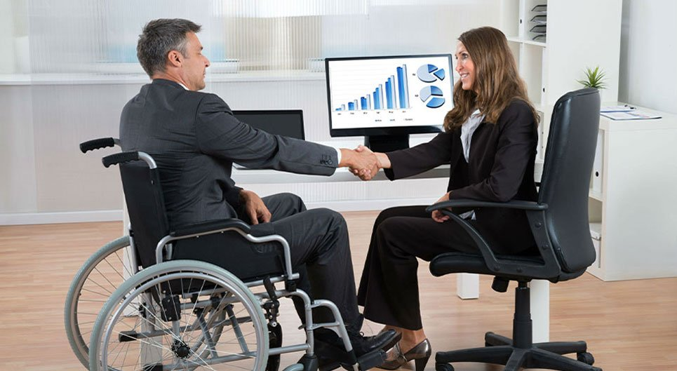 Man wearing a suit in a wheelchair, shaking the hand of a business woman