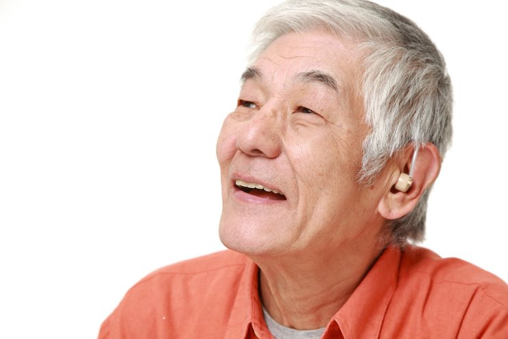 Happy white haired Asian man, who is wearing a hearing-aid