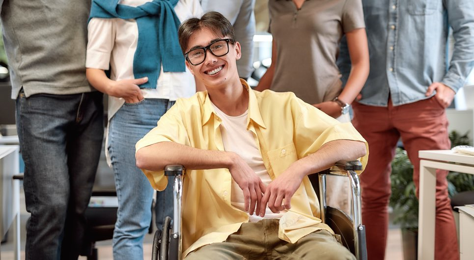 A smiling Asian man with thick glasses in a wheelchair in front of his work mates