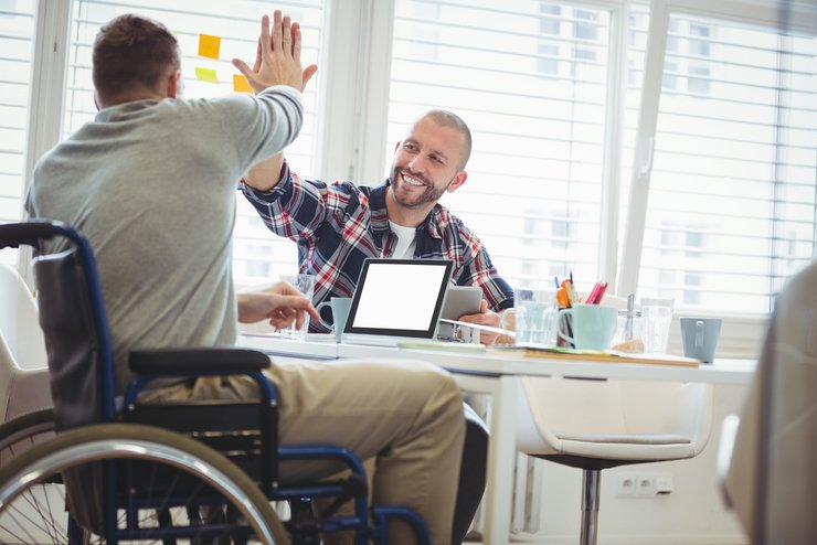 A man sitting in a wheelchair at a table gives another seated smiling man a high five