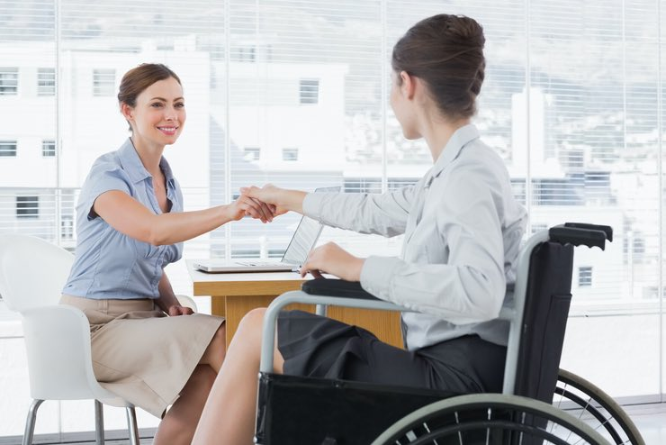 """It's a deal"". A woman in a wheelchair, shakes the hand of another woman over a desk"