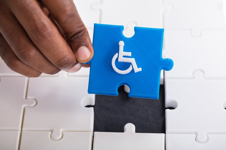 A black hand holds up a blue jigsaw piece with a white disability icon