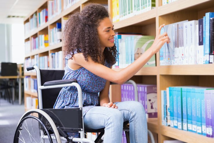Young woman in a wheelchair browsing through resouces