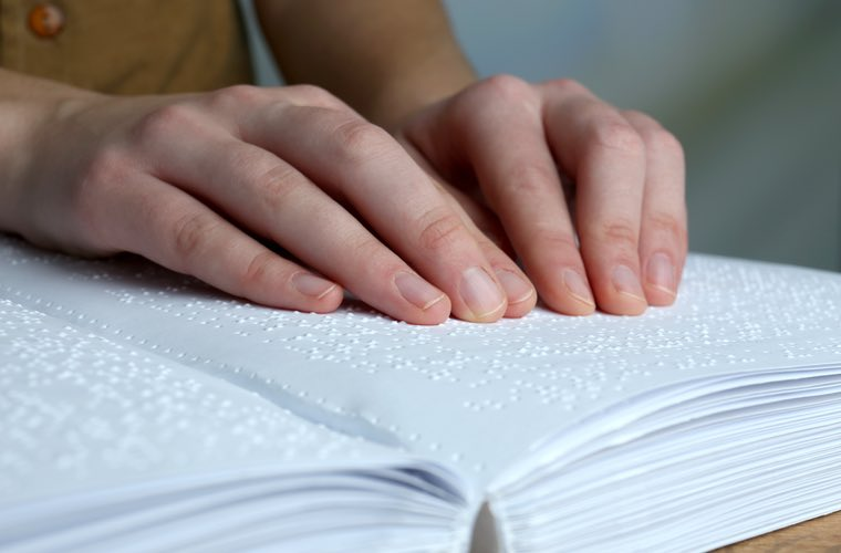 Hands reading a page in an open book of Braille .