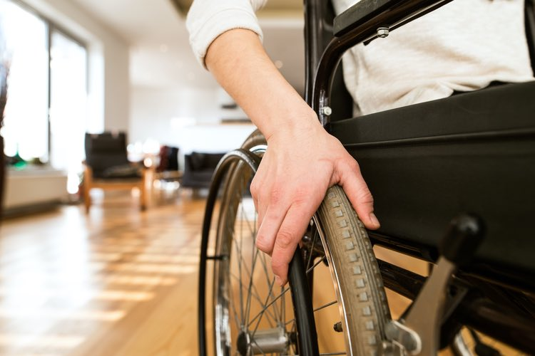 Young woman's hand gripping the wheel of her wheelchair