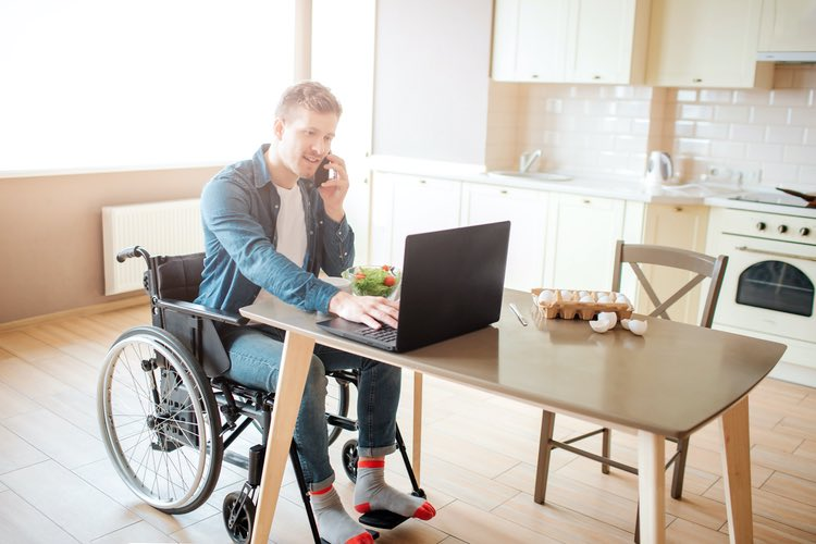 Man in a wheelchair works on a laptop on a table, while speaking a phone