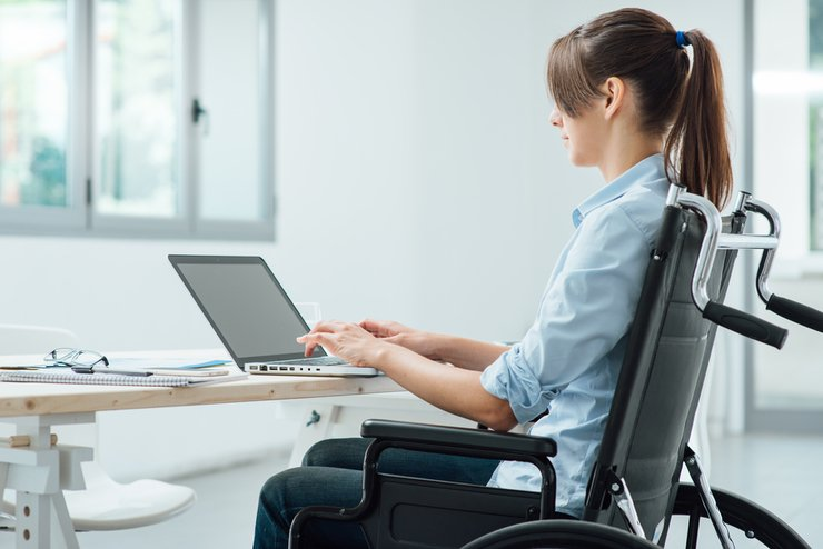 A woman in a wheelchair busy on a laptop