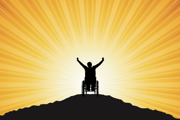 Silhouette of a guy on a wheelchair greets the dawn with raised arms