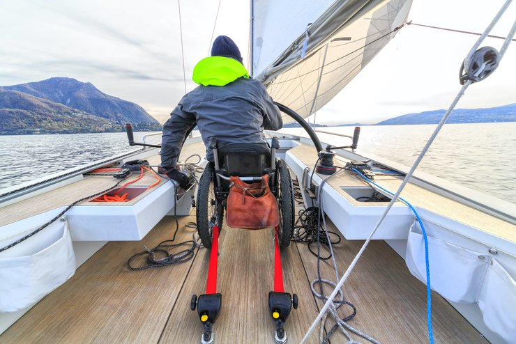 A guy in a wheelchair sailing a boat