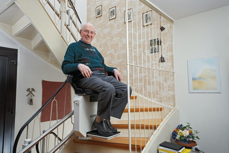 Smiling senior man partway up a stairlift