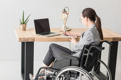 A young woman in a wheelchair, looking at a laptop and taking notes
