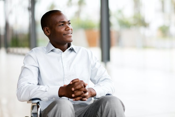 An African-American man in a wheelchair looks toward the horizon with a hopeful smile.