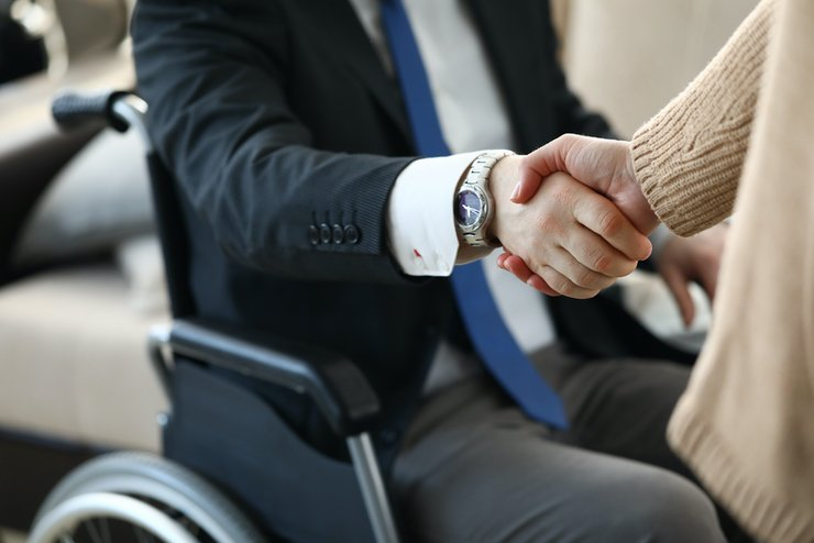 A person in a wheelchair shaking another person's hand