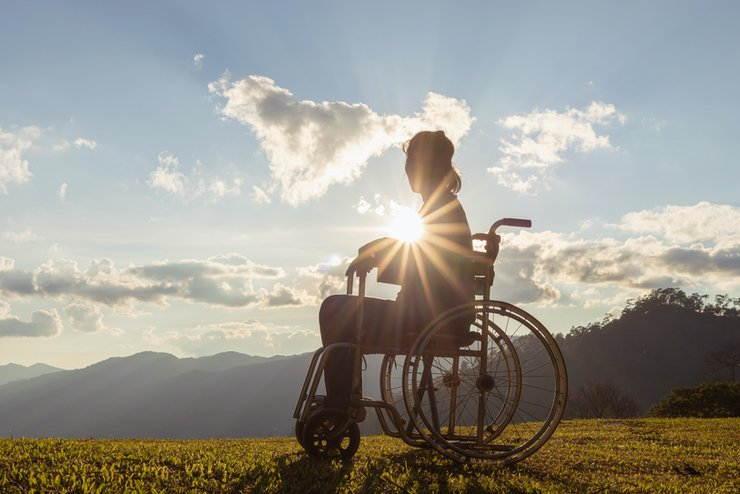 A woman in a wheelchair photographed against a sunny sky
