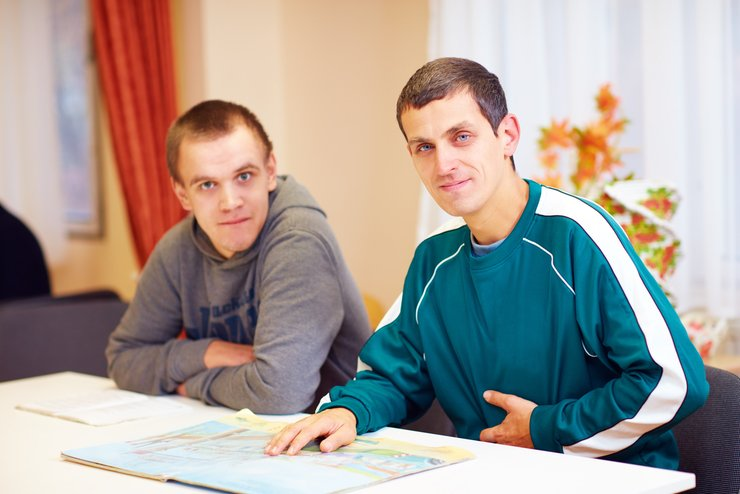 Two guys, who live with disabilities, meeting at a table