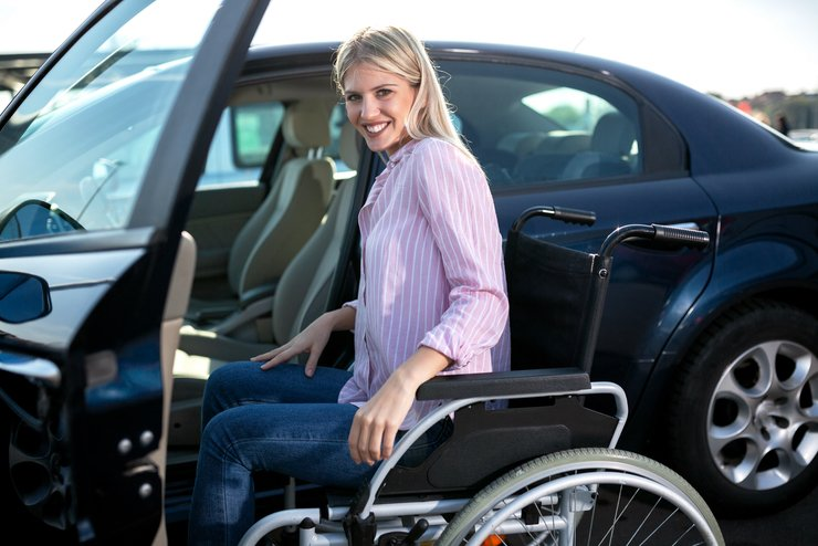 A smiling woman in a wheelchair about to self-transfer into a car