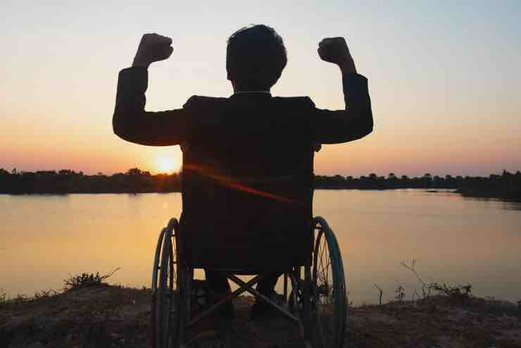 A man in a wheelchair celebrating on a lakeshore