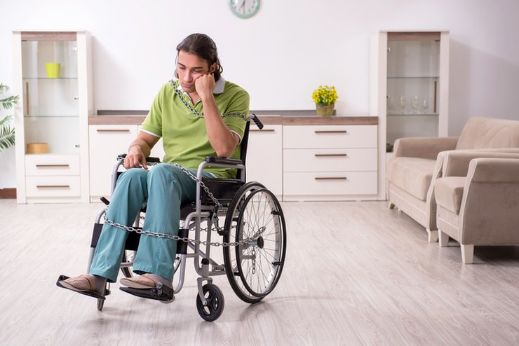 A depressed guy in a wheelchair in a lounge room