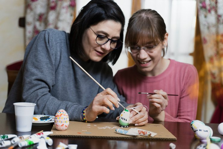 Two women work on decorating an egg.
