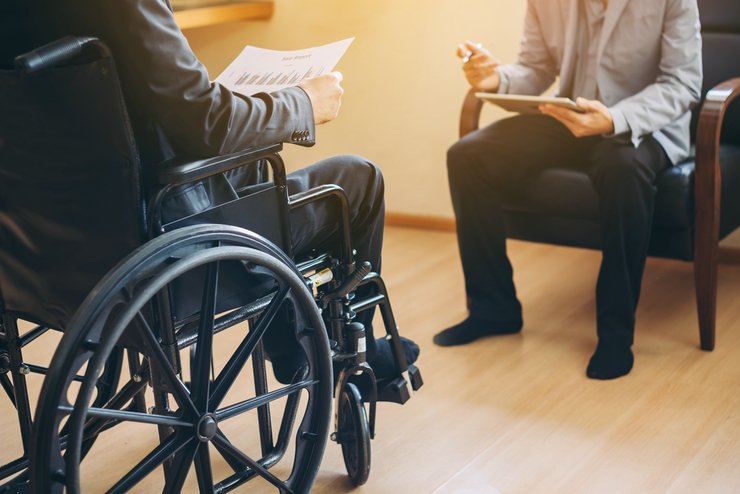 A man in a wheelchair in a planning meeting