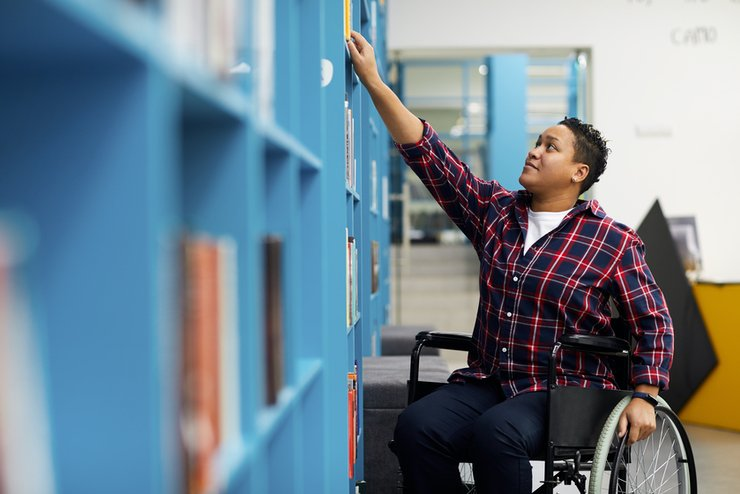 A black woman in a wheelchair, reaching up to a library bookshelf
