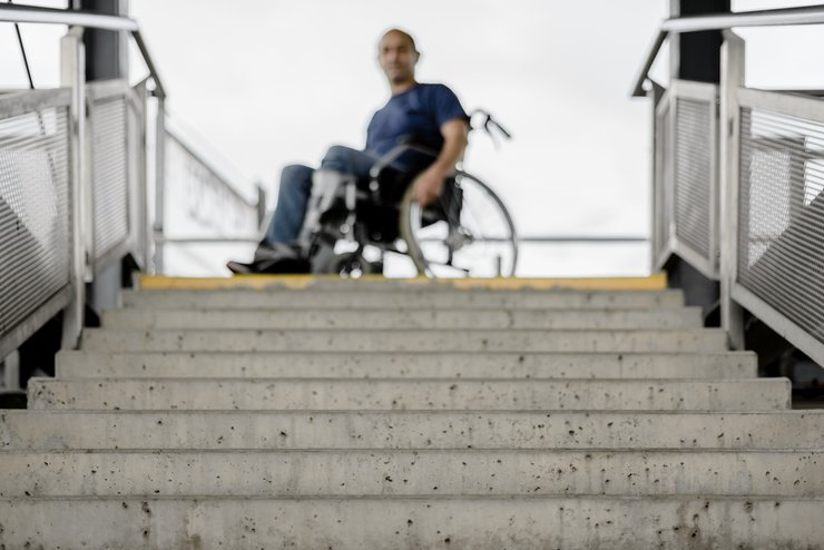 A man in a wheelchair looks down a tall flight of concrete stairs