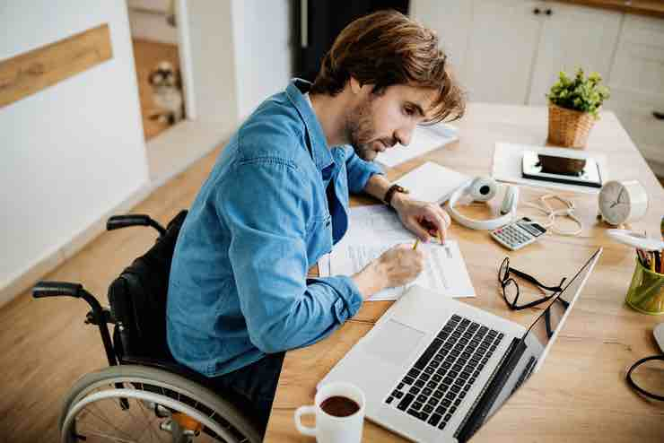 A young man in a wheelchair in his study working on his laptop