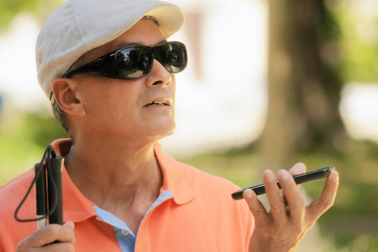 A sight impaired man using voice control on his smartphone.