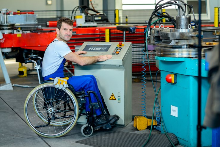 A man in a wheelchair looks around to us from an engineering machine