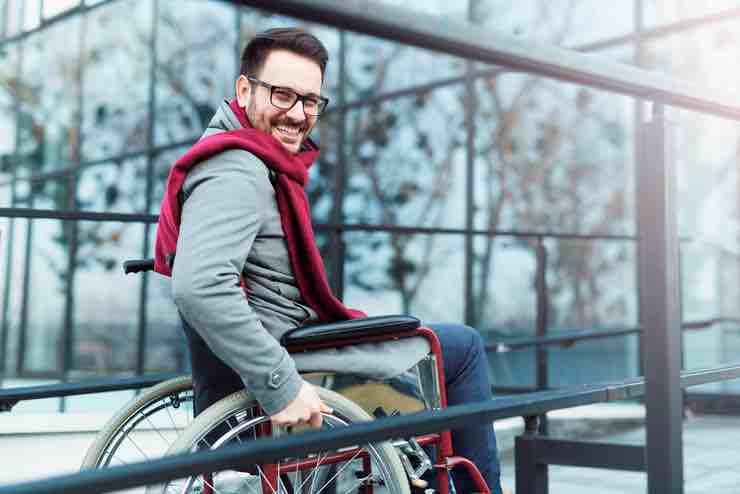 Grinning hip guy wearing a scarf and sitting in a wheelchair arriving at a mirrored building