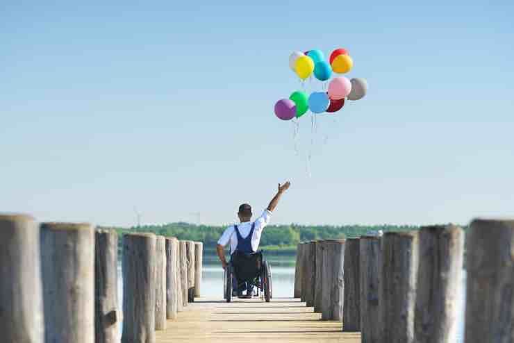 A man wearing overalls, in a wheelchair and holding a bunch of balloons, at the end of a wooden pier