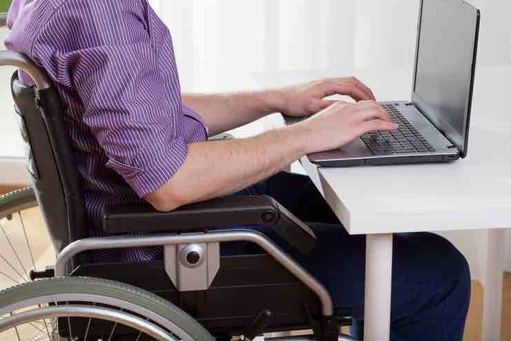 A man in a wheelchair wearing a striped shirt typing on a laptop