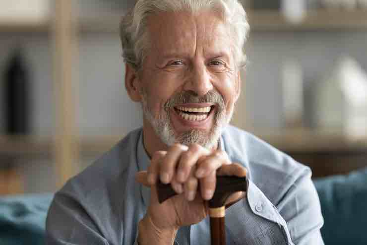 Laughing, white-haired and bearded man holding a walking stick