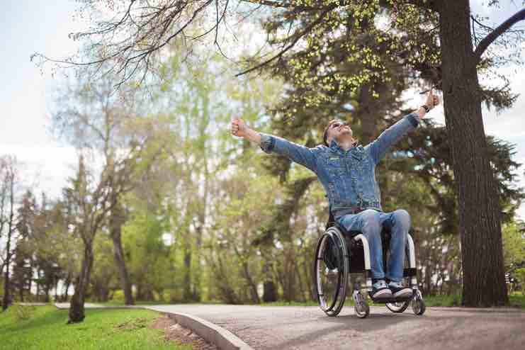 Man in a wheel chair on a down slope in a sunny leafy park, with his arms thrown wide in exaltation.