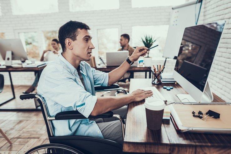 A man in a wheelchair gestures emphatically towards a computer