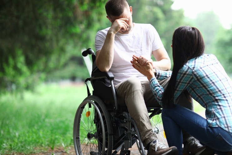 A man in a wheelchair bent by grief, consoled by a kneeling carer