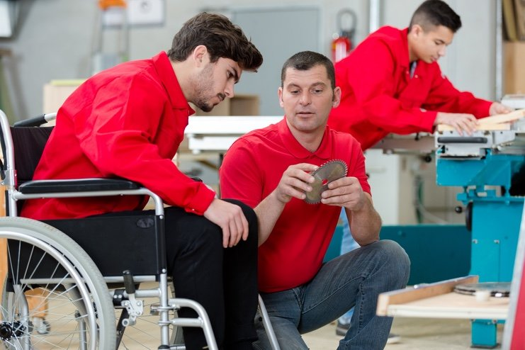 A worker in a wheelchair in a carpenters workshop
