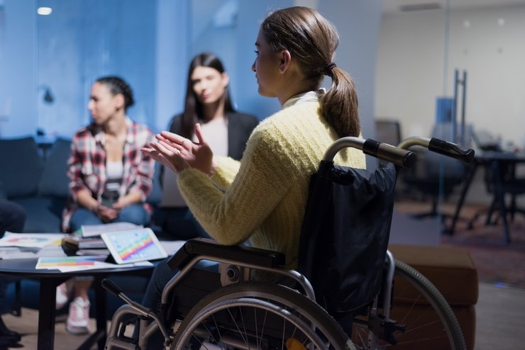 A woman in a wheelchair speaking at a workshop