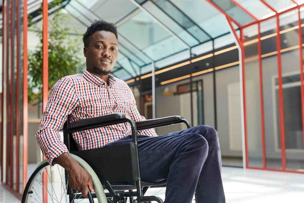 A man with a positive expression in a wheelchair in a bright and airy corridor