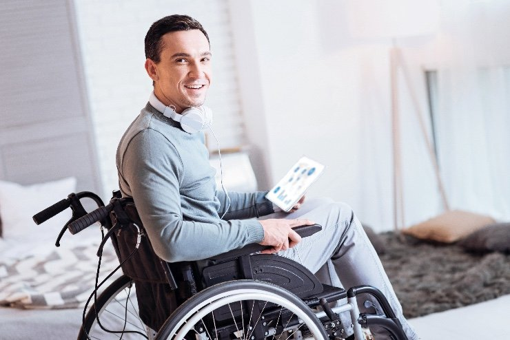 A handsome man in a wheel chair a smile on his face and turning head while looking at camera