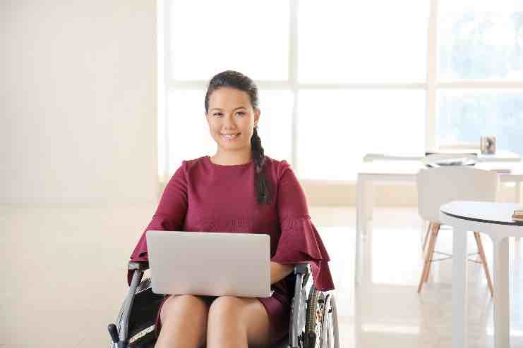 A smiling Asian woman with a laptop on her lap