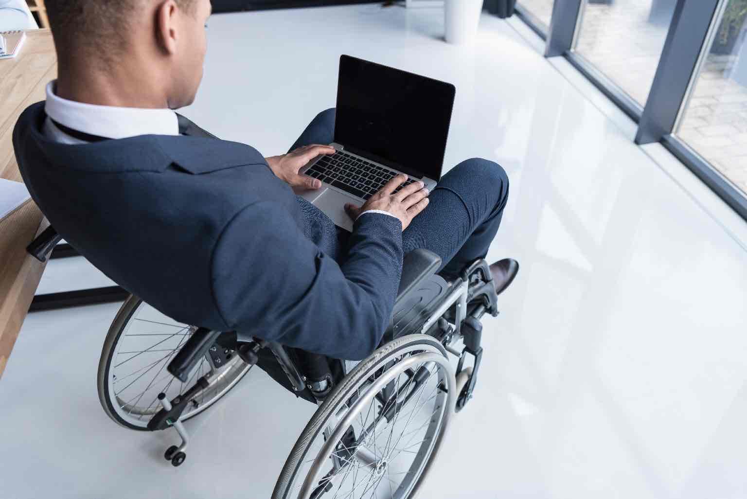 Cropped shot of disabled Black man businessman typing on laptop