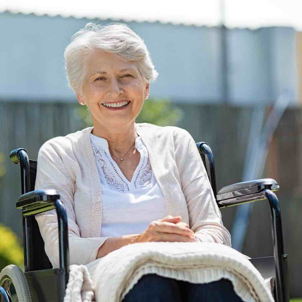 An old woman smiling as she is siting outside in a wheelchair