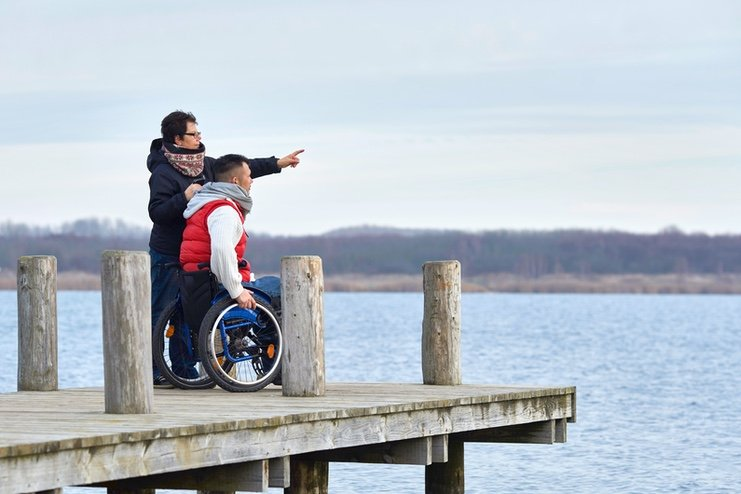 A man in a wheelchair and a carer looking out from a quay