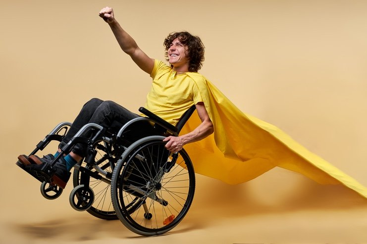 A young man in a wheelchair with a cape, with his fist raised ready to take off