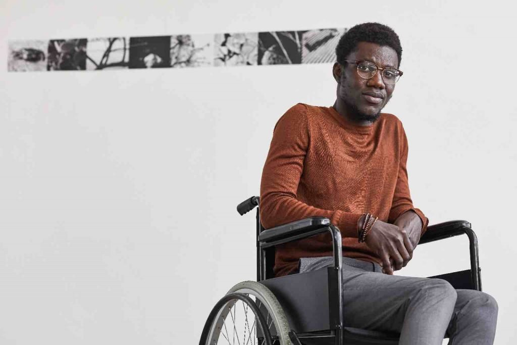 Minimal portrait of young black man using wheelchair and looking at camera while posing against white wall in modern art gallery.
