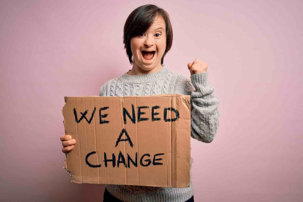 """A young chanting woman with Down Syndrome holds a sign that reads, """"WE NEED A CHANGE"""""""